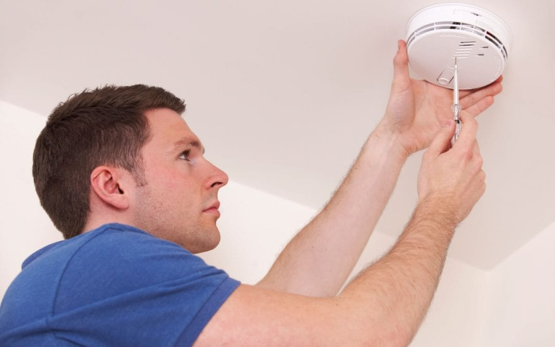man installing detector using correct smoke detector placement
